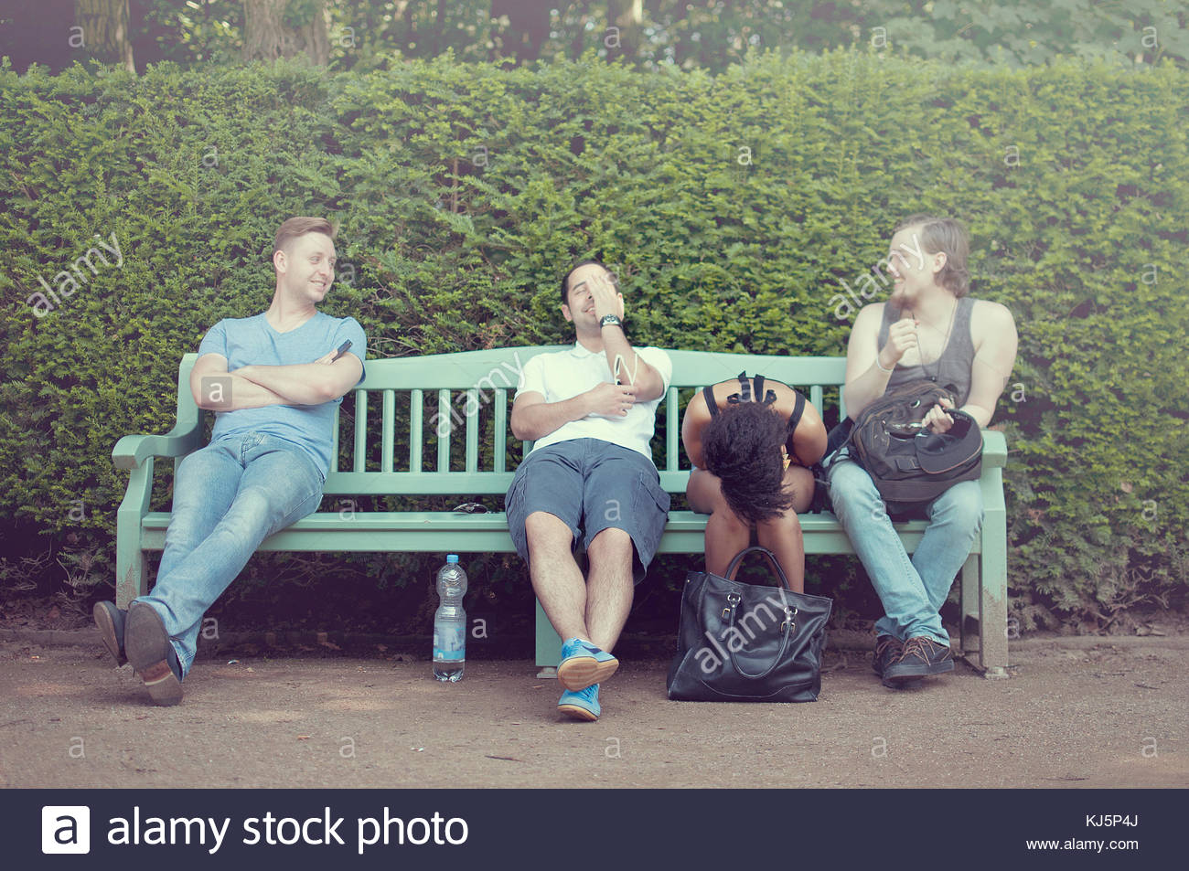 Group of happy friends on a bench laughing - Stock Image