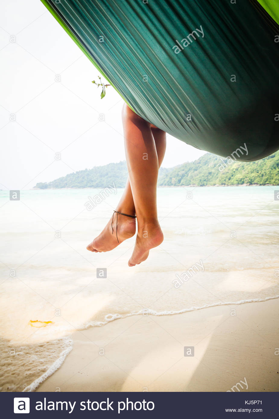 attractive brunette on sandy beach relaxing - Stock Image