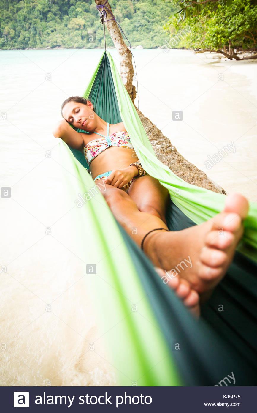 attractive brunette on sandy beach relaxing in hammock - Stock Image