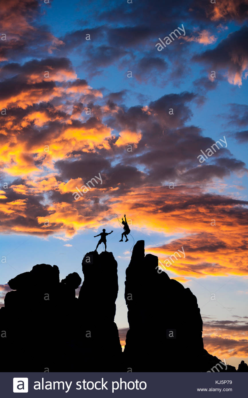 Climber jumping from one rock to another Stock Photo