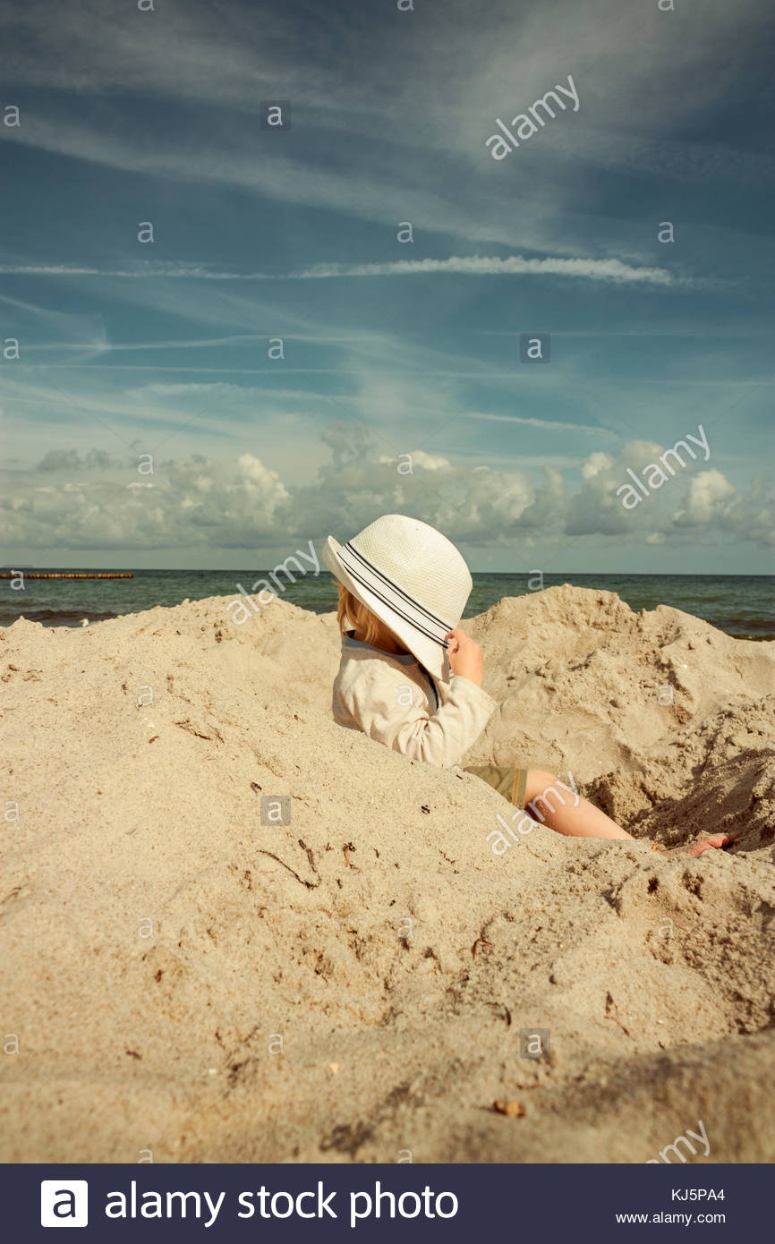 Child sitting in a hole on the beach, face covered by a hat - Stock Image