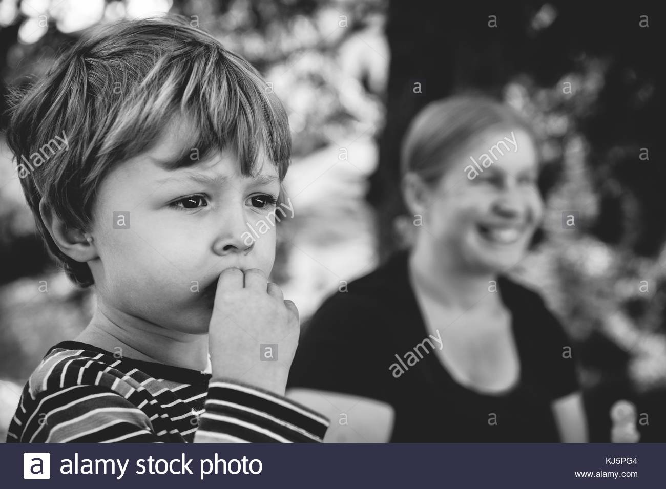Picture of little boy with mother in the background - Stock Image
