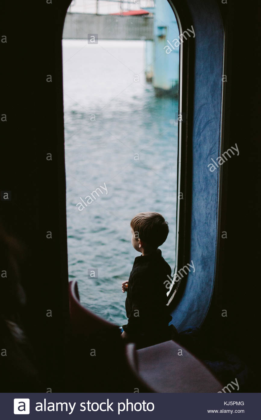 child looking through port hole - Stock Image