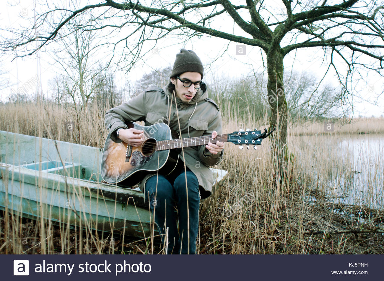 Guy playing guitar sitting in a harsh outdoor environment - Stock Image