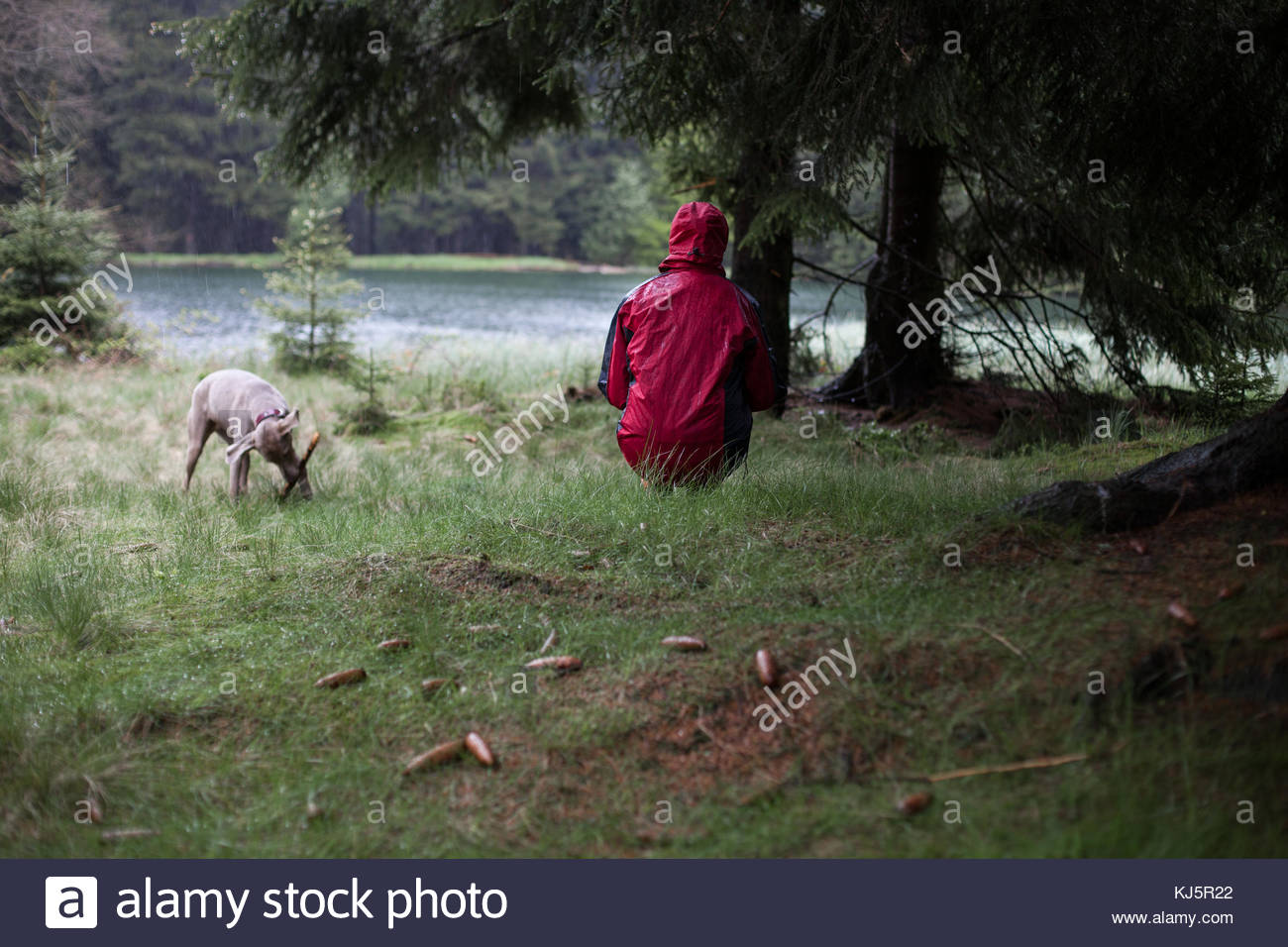 woman in anorak jumping by water - Stock Image