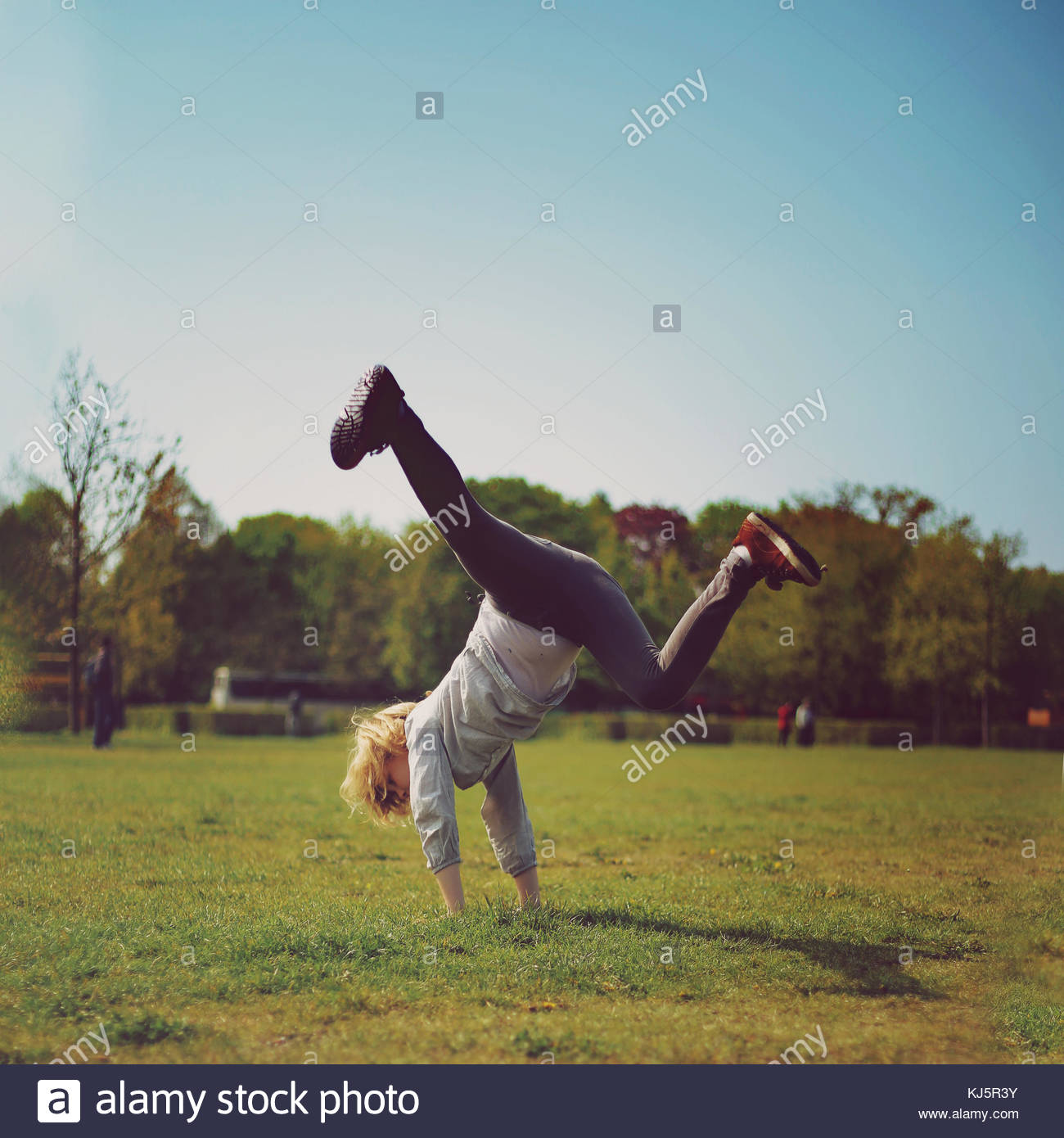 Boy doing a cartwheel - Stock Image