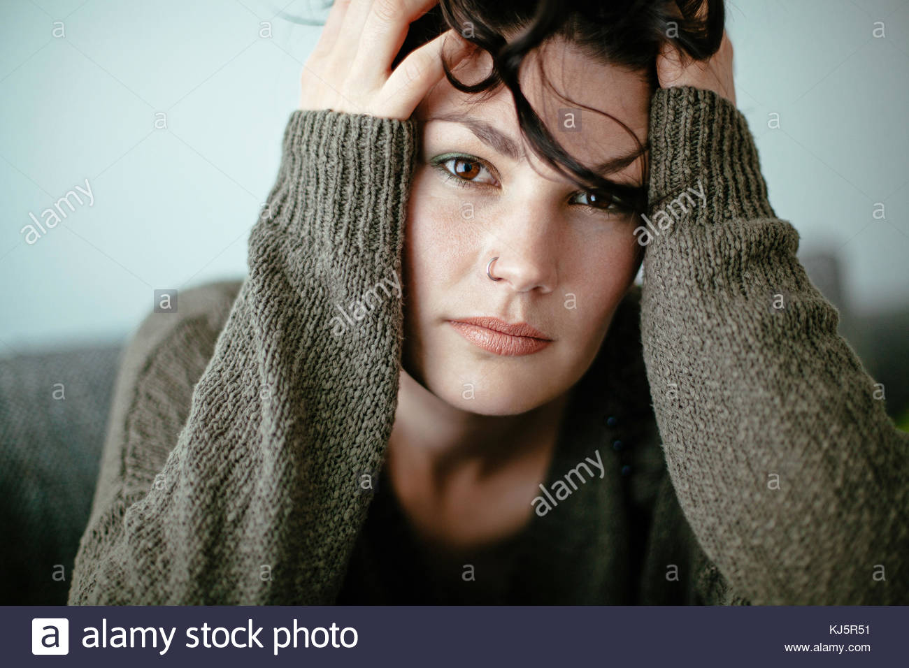 woman with head in hands - Stock Image