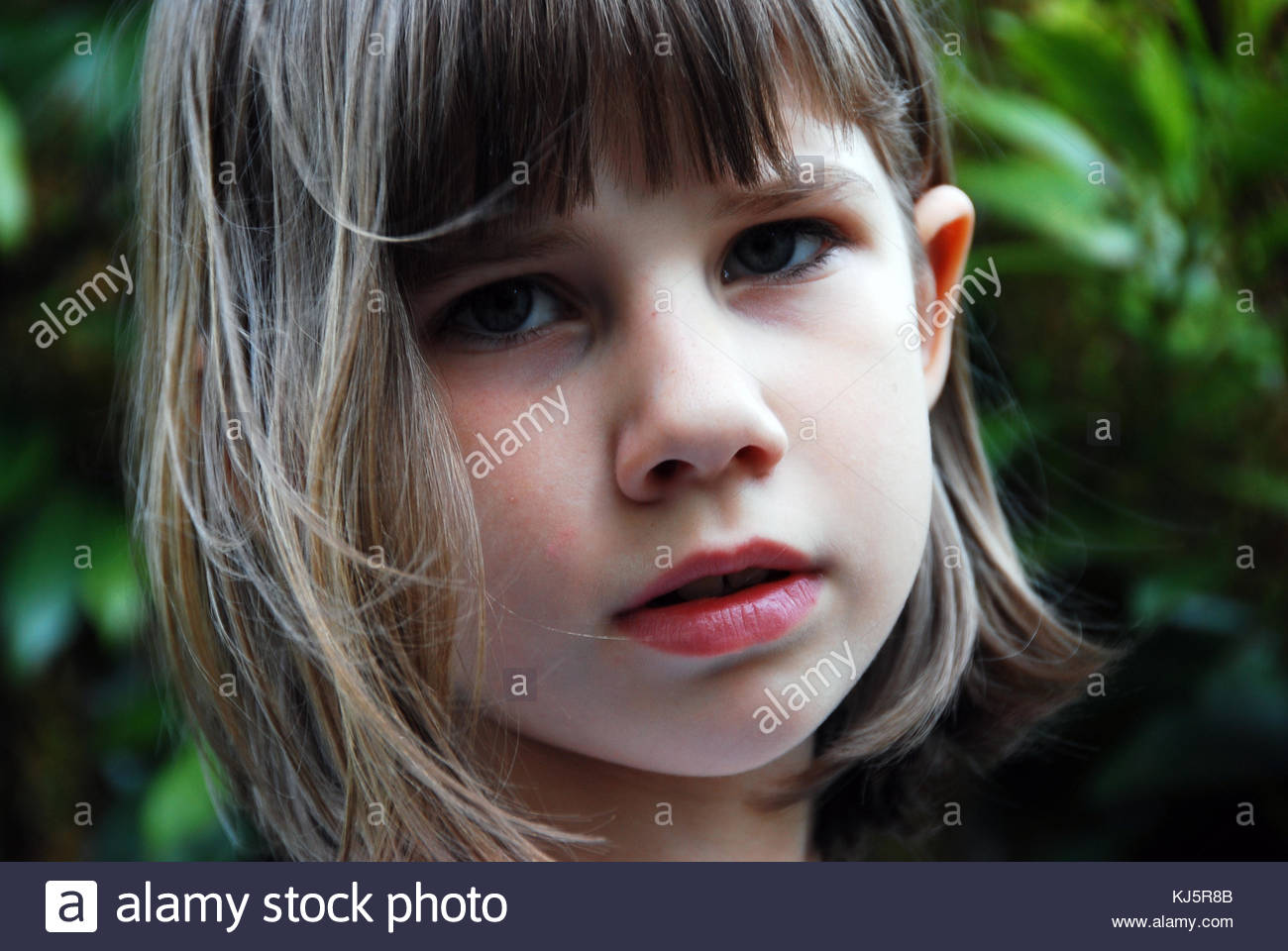 child's face with green background - Stock Image