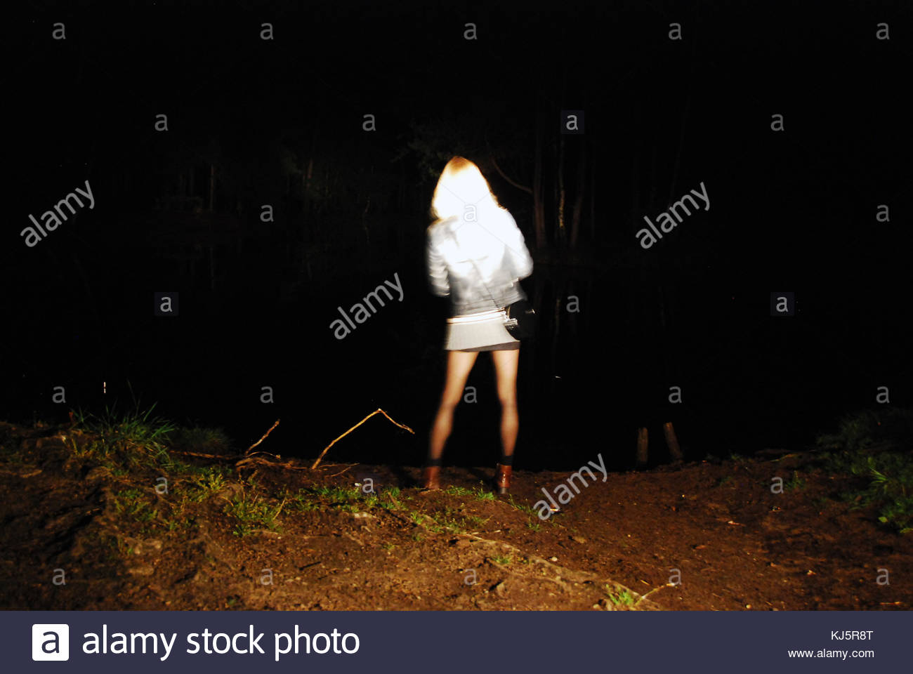 young woman in dark with short skirt - Stock Image