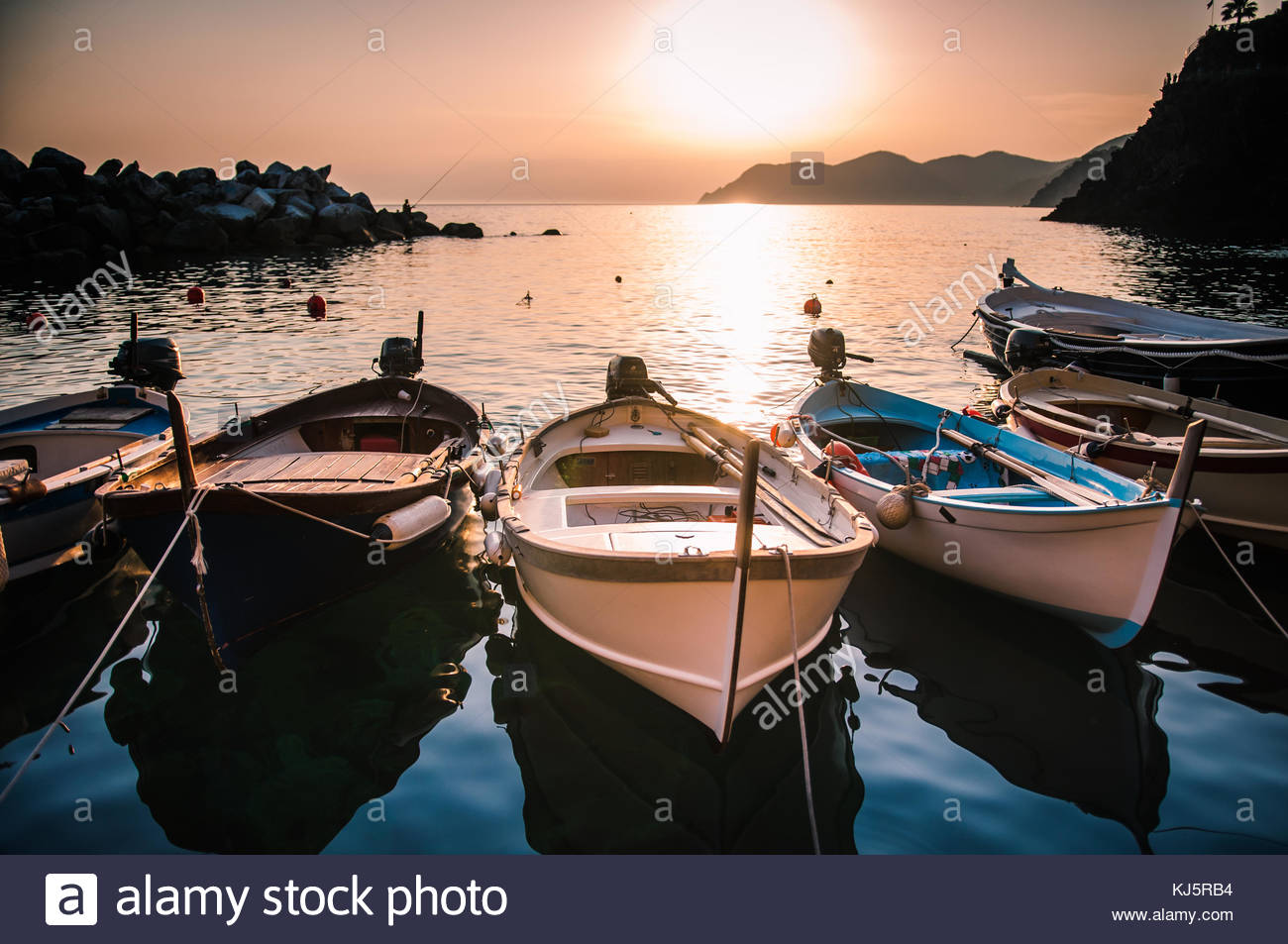 Row of boats at sunset - Stock Image
