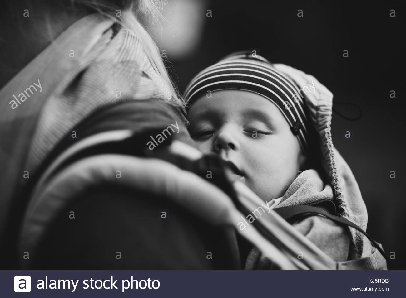 Baby sleeping in sling on mother's back - Stock Image