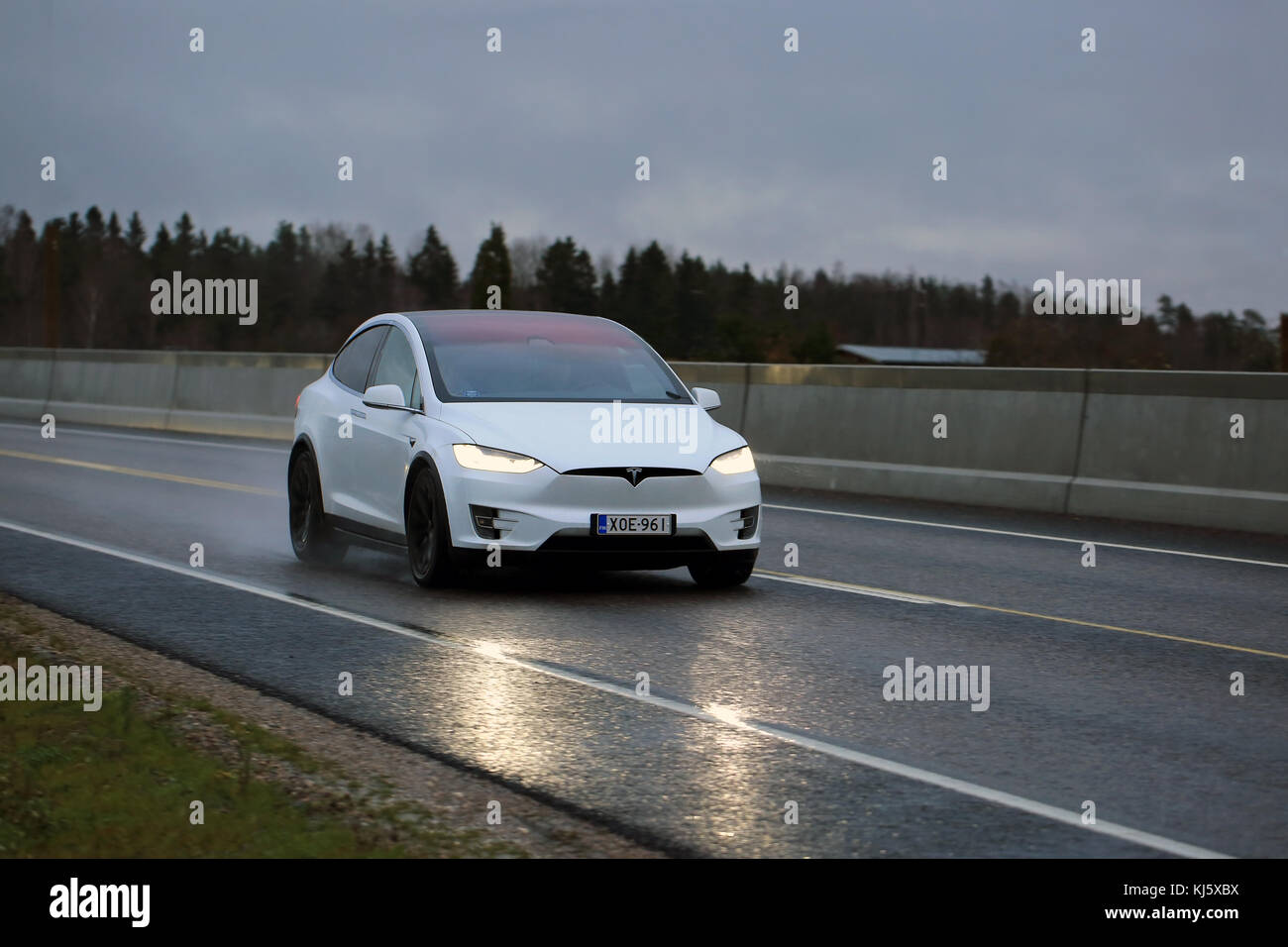 SALO, FINLAND - NOVEMBER 18, 2017: White Tesla Model X electric car moves along wet road in the evening. - Stock Image