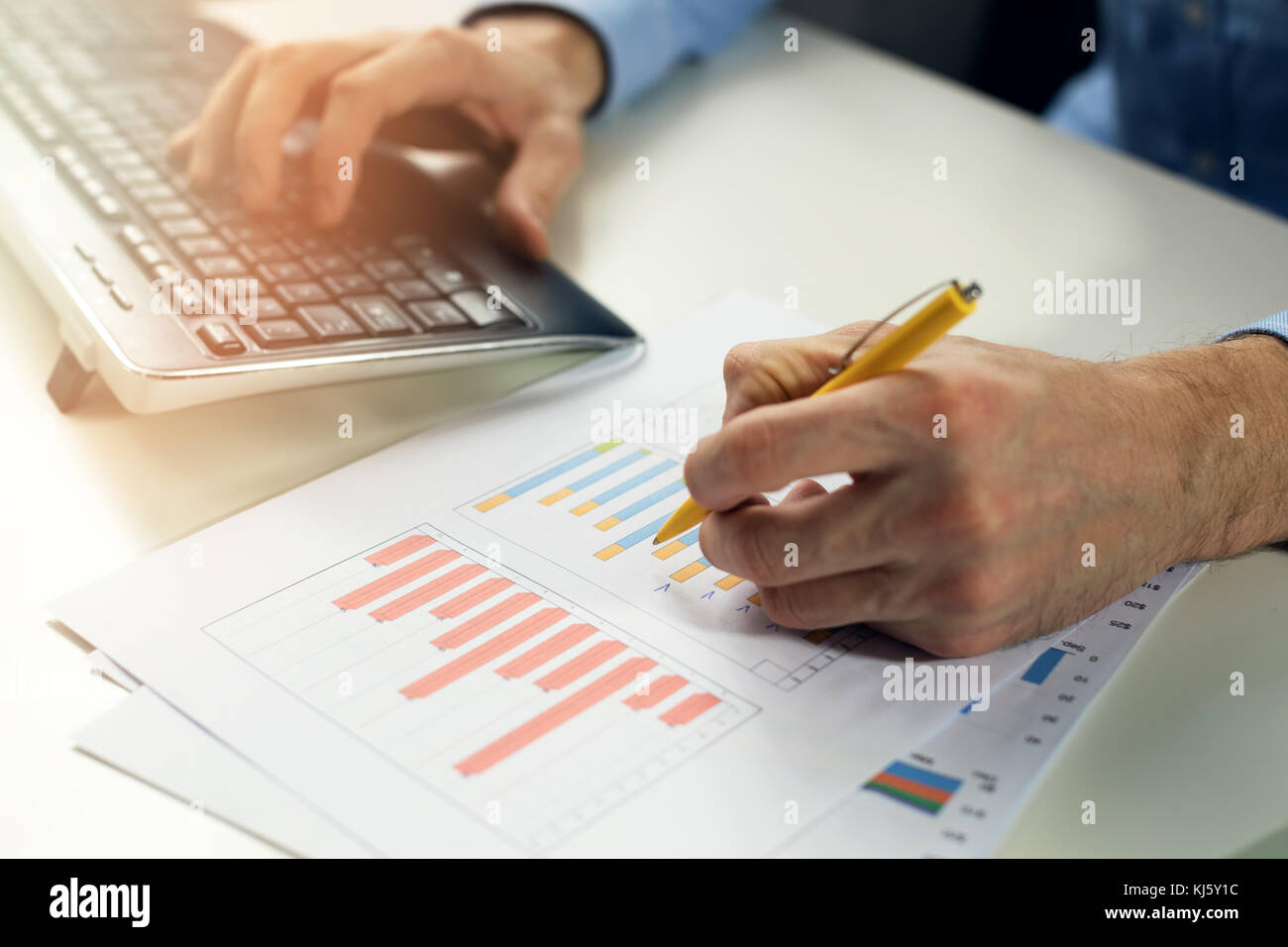 office clerk working with statistical reports and entering data into a computer - Stock Image