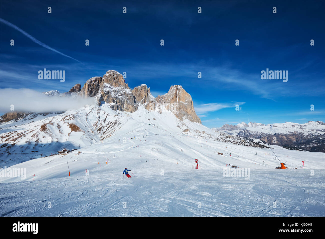 View of a ski resort piste with people skiing in Dolomites in Italy - Stock Image