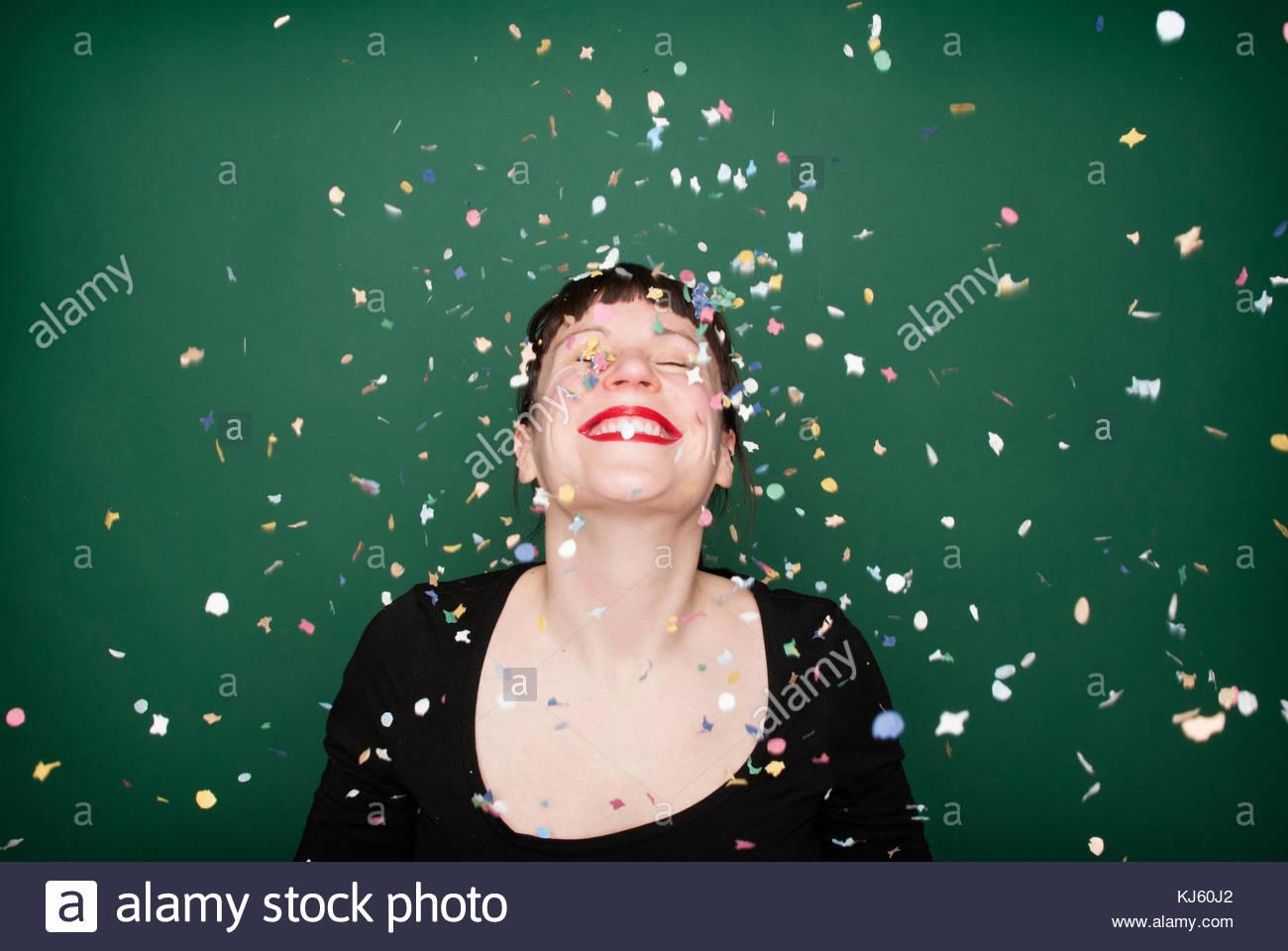 Happy woman with confetti - Stock Image