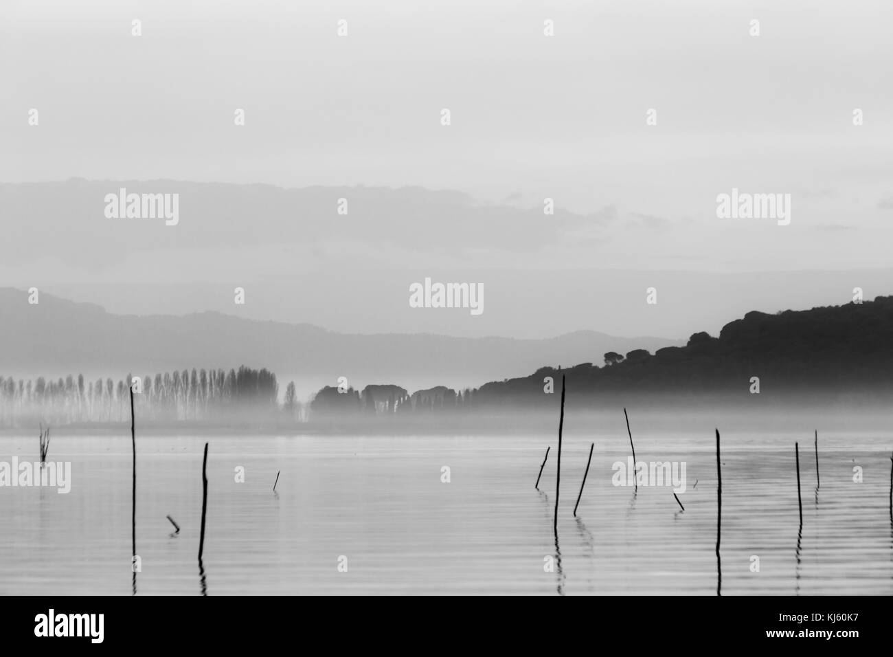 A lake at dusk, with soft tones in the sky and water and an island in the middle of mist - Stock Image