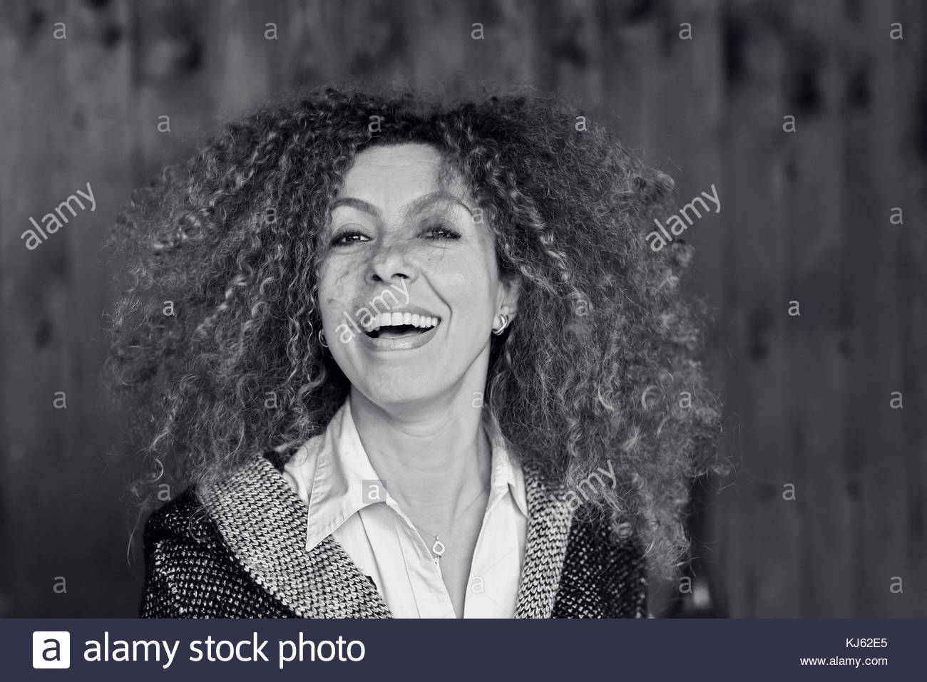 Curly haired middle aged woman enjoyment of life - Stock Image