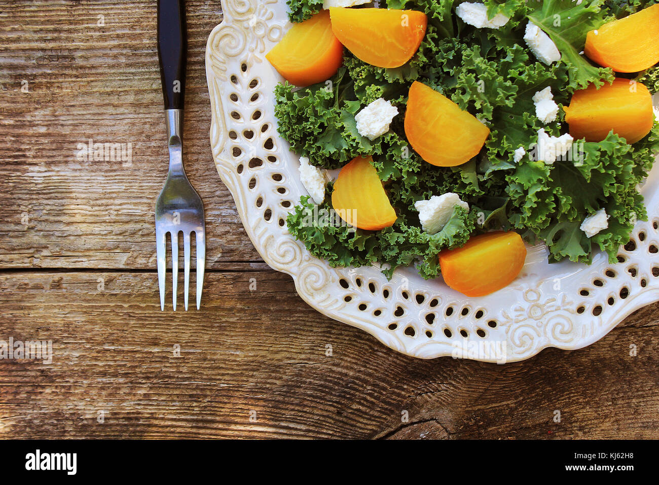 Healthy Beet Salad with fresh kale lettuce, nuts, feta cheese on wooden background. Top view - Stock Image