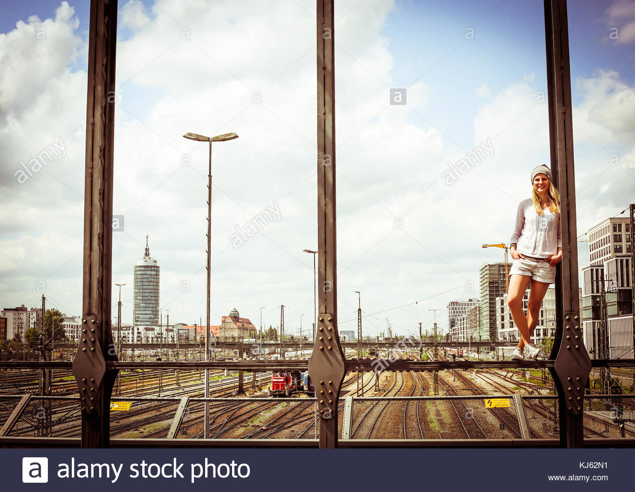 Smiley blonde woman standing over the rim of a bridge overlooking the railways - Stock Image