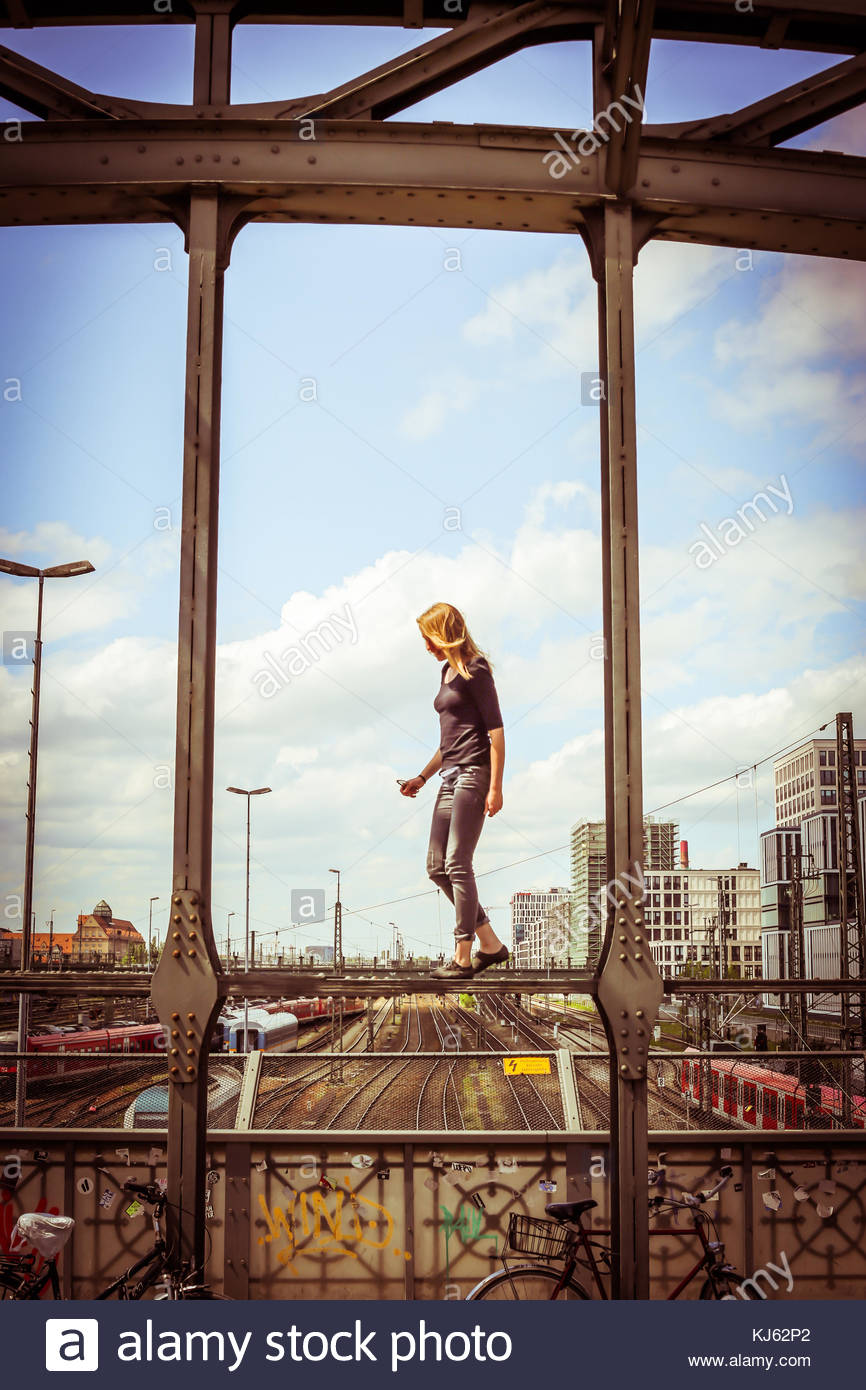 blonde woman standing over the rim of a bridge overlooking the railways - Stock Image