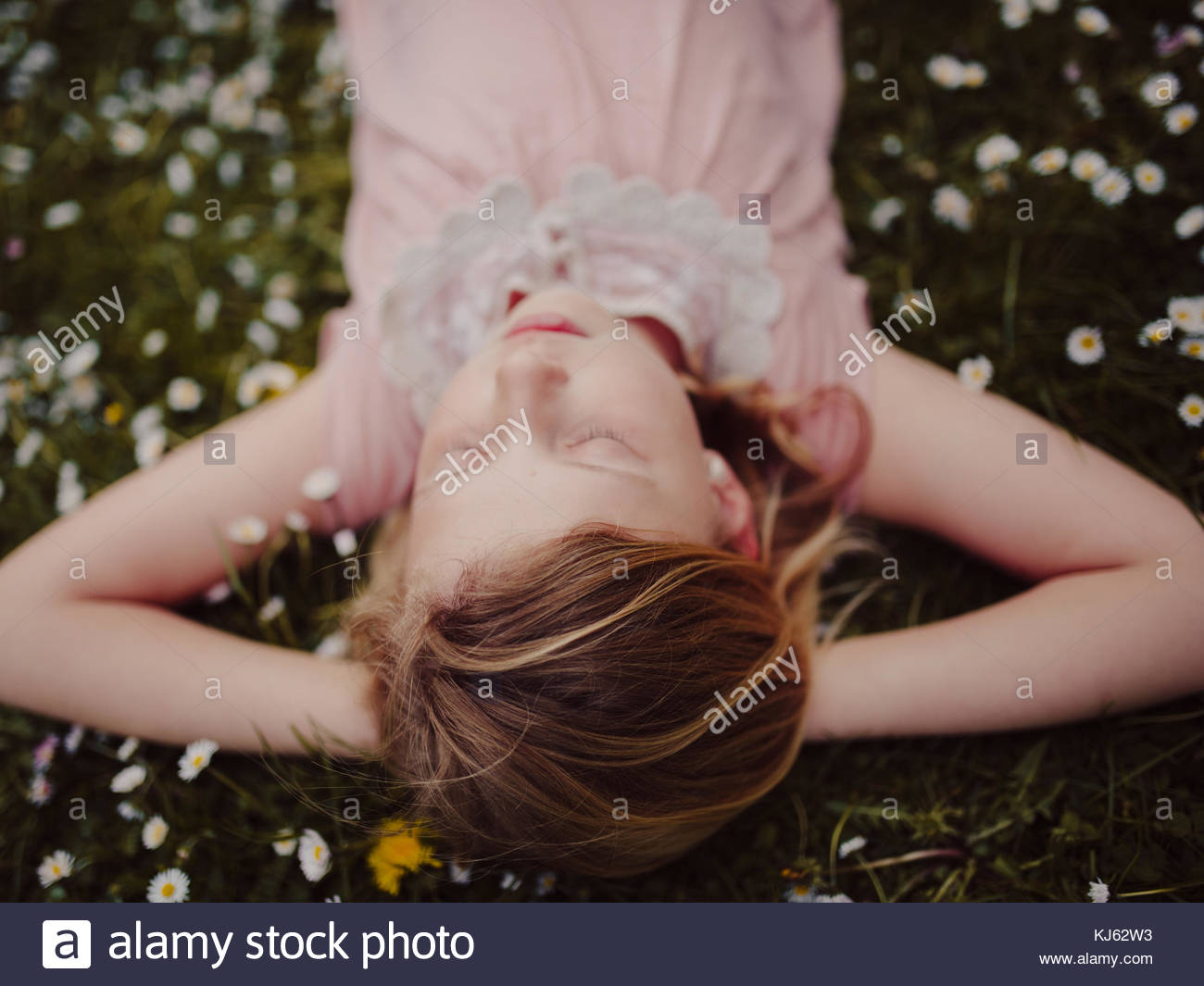 Young girl in pink dress laying in the grass - Stock Image