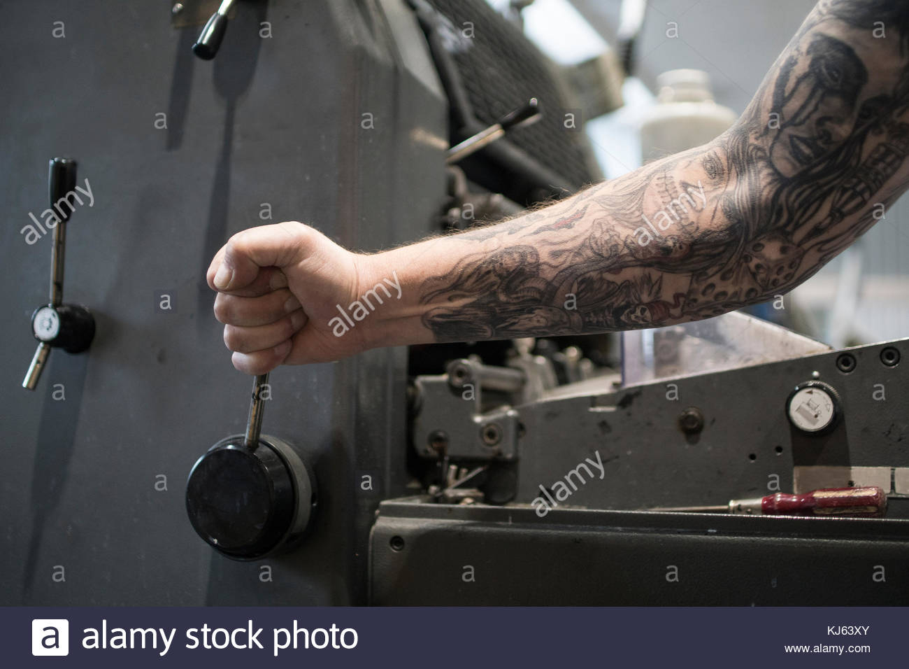 Strong tattooed arm pulling a lever - Stock Image