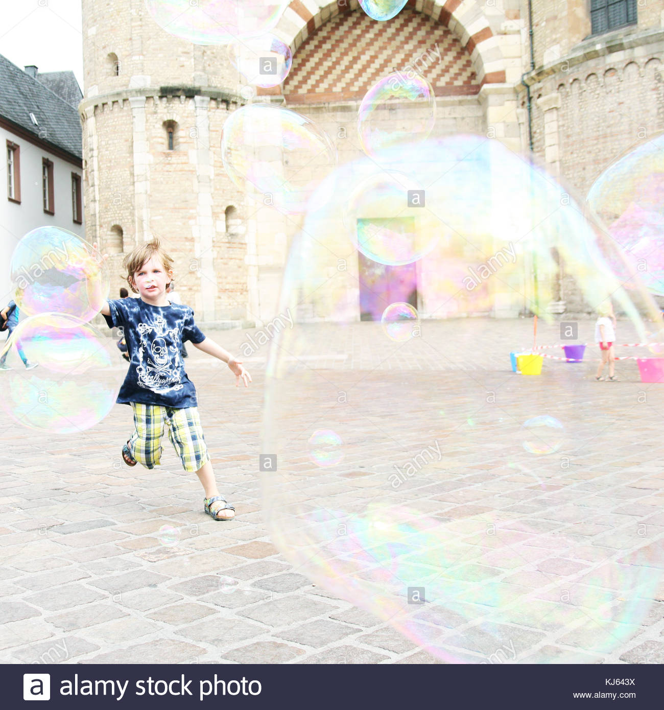 Young boy playing with soap bubbles in the square - Stock Image