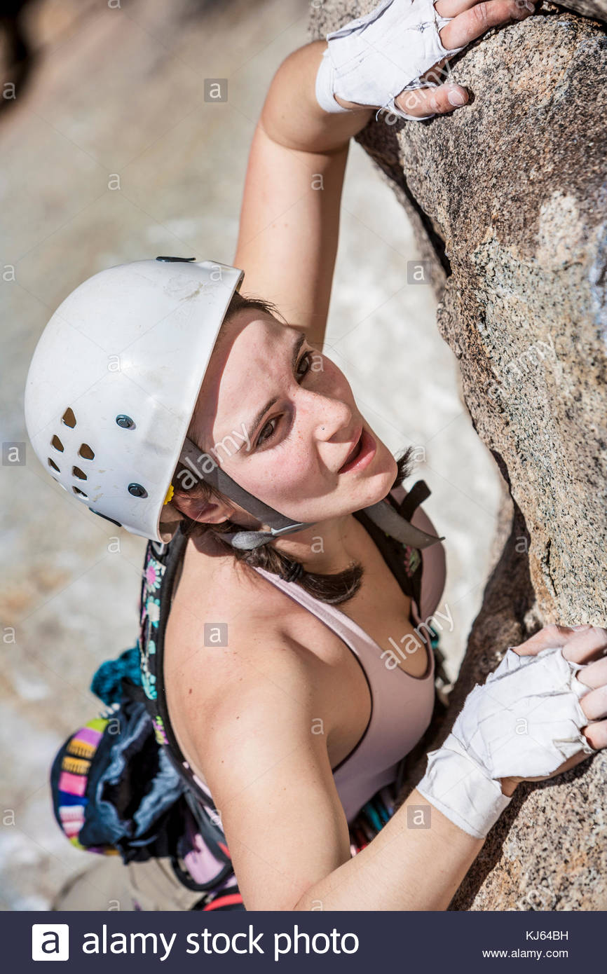 Woman Climber holds on tight and enjoy the climb - Stock Image