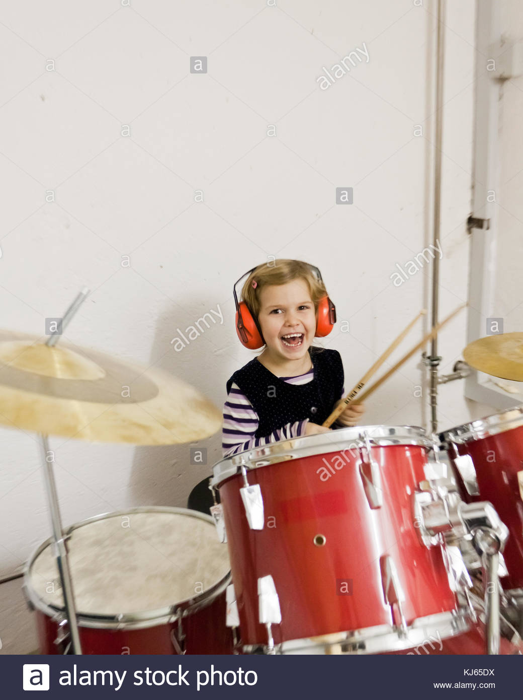 Little girl enjoying playing the drums - Stock Image