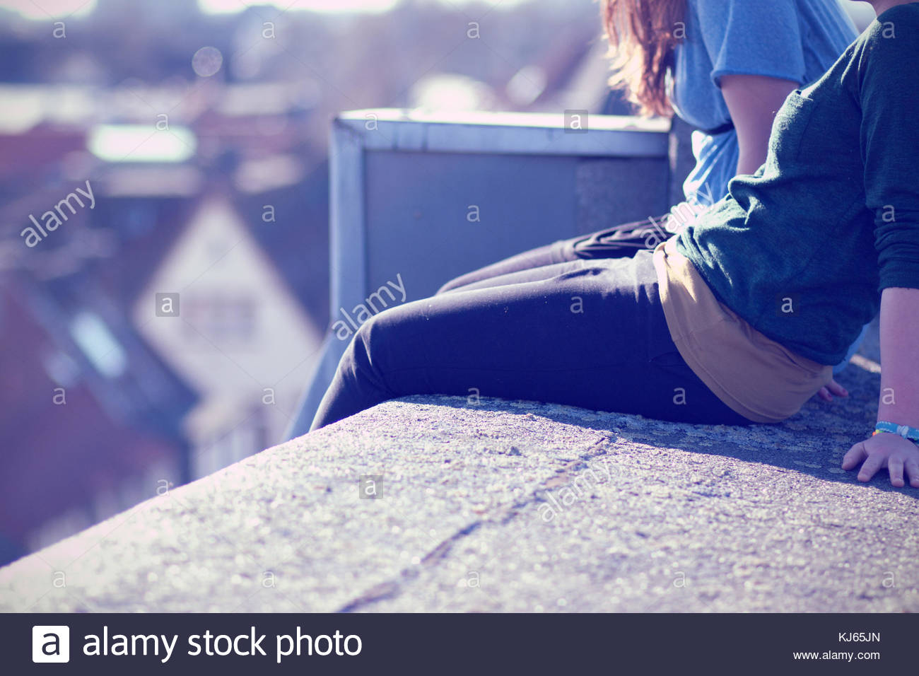 Two friends on the rooftop of a building. Just body - Stock Image
