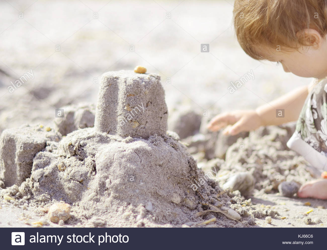 Child making sand castle - Stock Image
