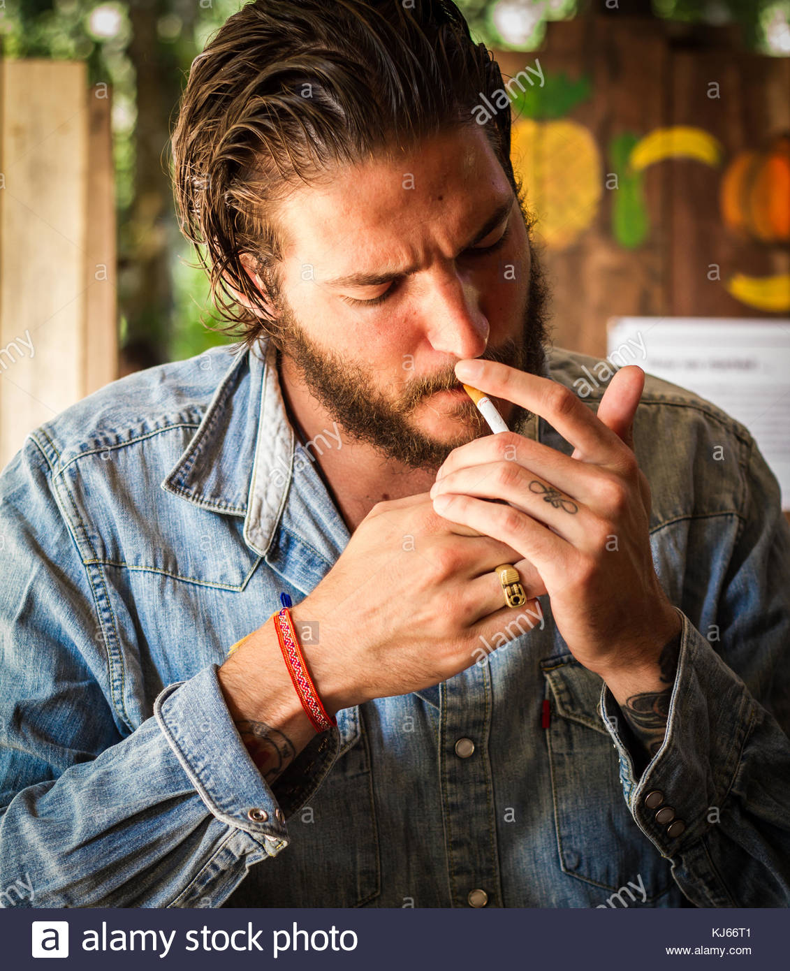 young man with beard smoking in sun - Stock Image