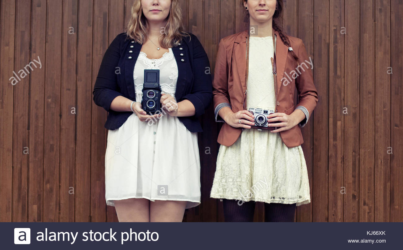 Young women with analogue cameras - Stock Image
