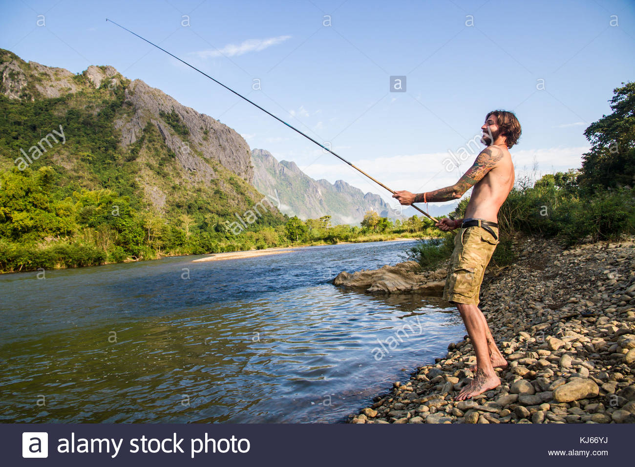 young man with beard fishing by river - Stock Image