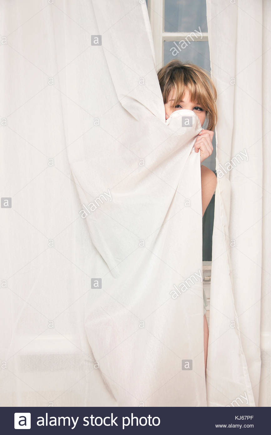 Woman smiling behind a white curtain - Stock Image