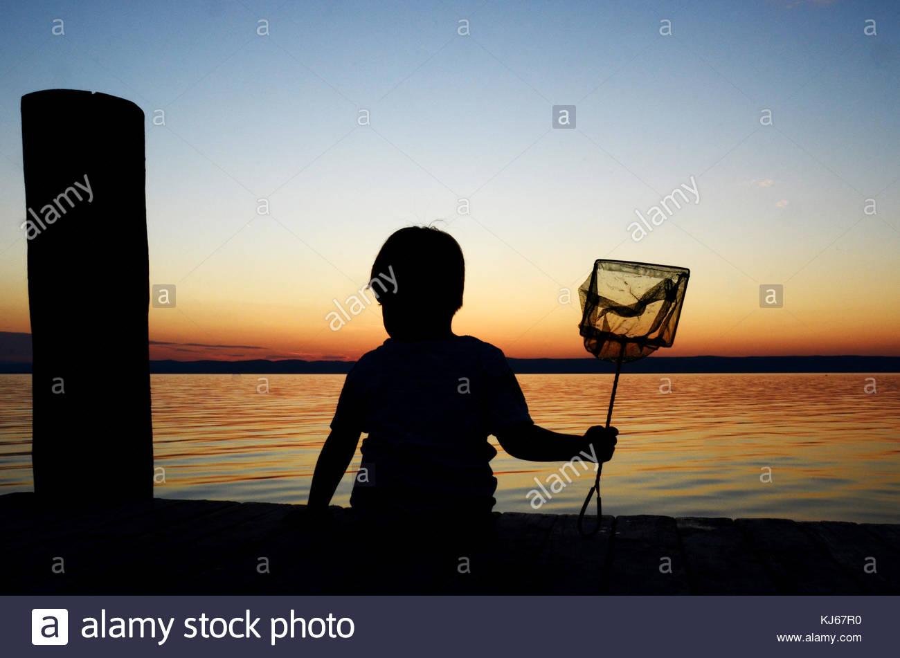 Toddler with landing net - Stock Image