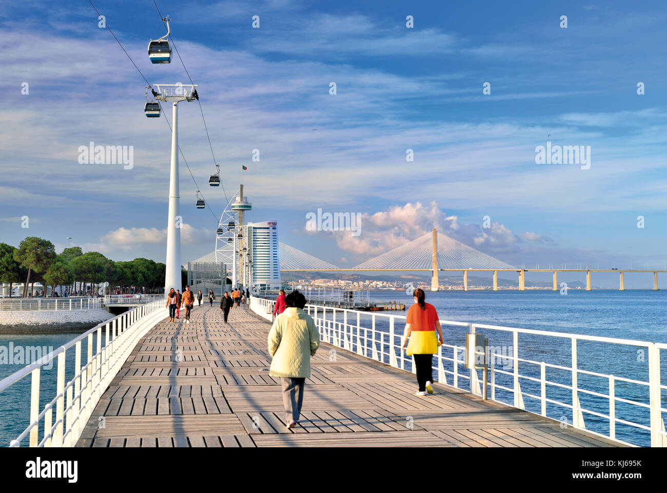 People passing pedestrian bridge surrounded by modern architecture, cable car lift and Vasco da Gama bridge - Stock Image