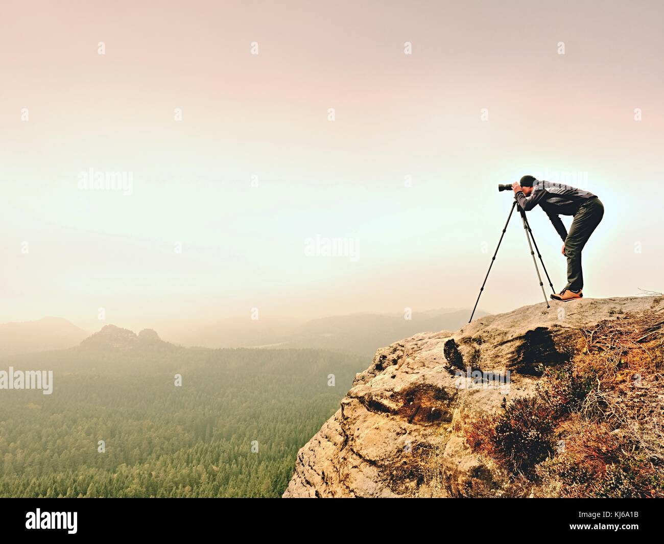 Professional photographer takes photos of misty landscape with mirror camera and tripod. Thick fog in autumnal countryside. - Stock Image