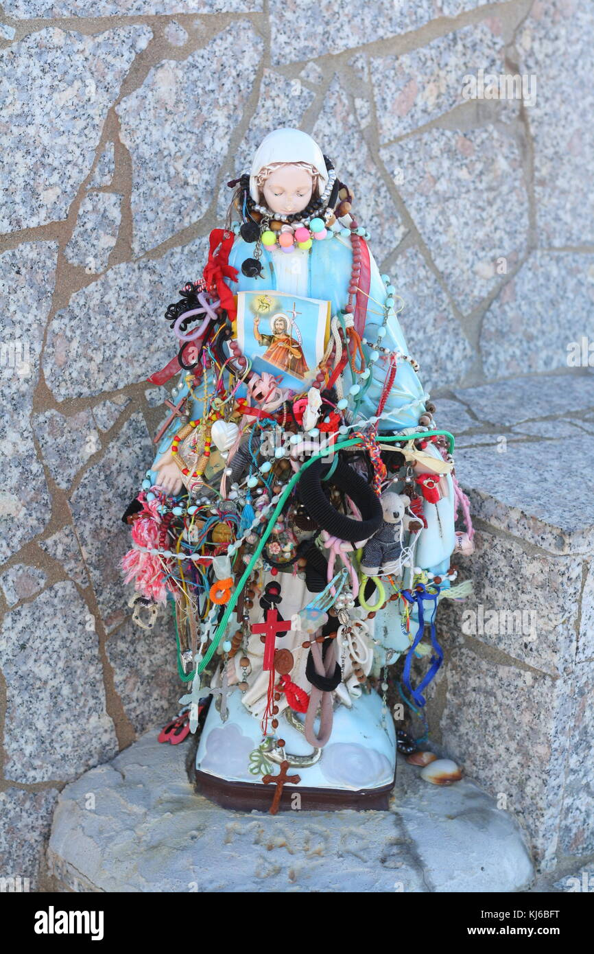 A religious maria doll with kitsch jewellery decoration. - Stock Image