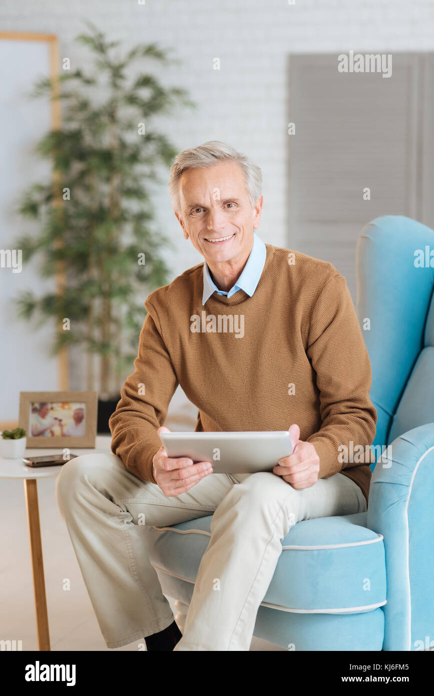Friendly looking old gentleman working on tablet computer - Stock Image