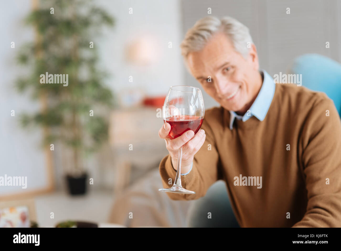 Happy old man enjoying his glass of red wine - Stock Image