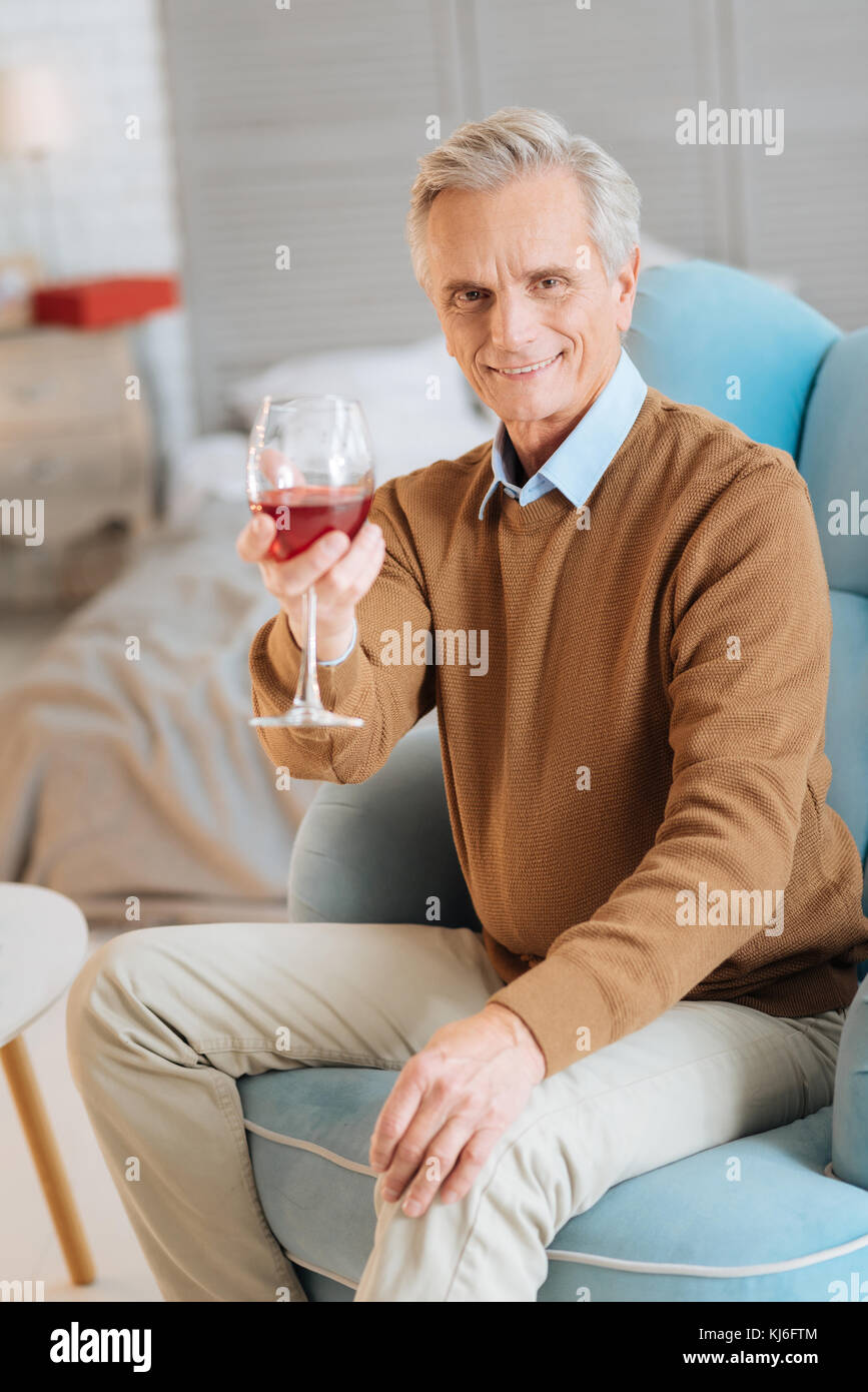 Smiling elderly gentleman drinking red wine at home - Stock Image