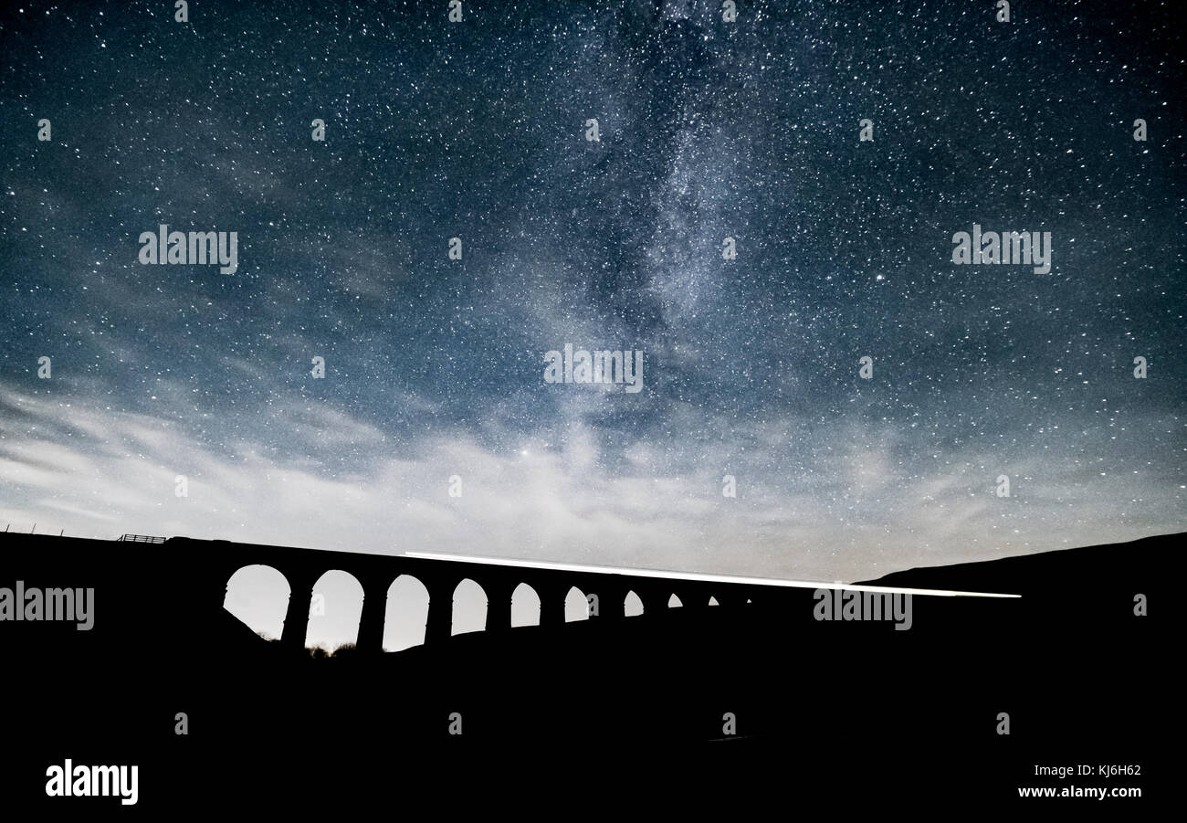 Long exposure of a train passing over Ribblehead Viaduct, whilst the incredible Milky Way rises above - Stock Image
