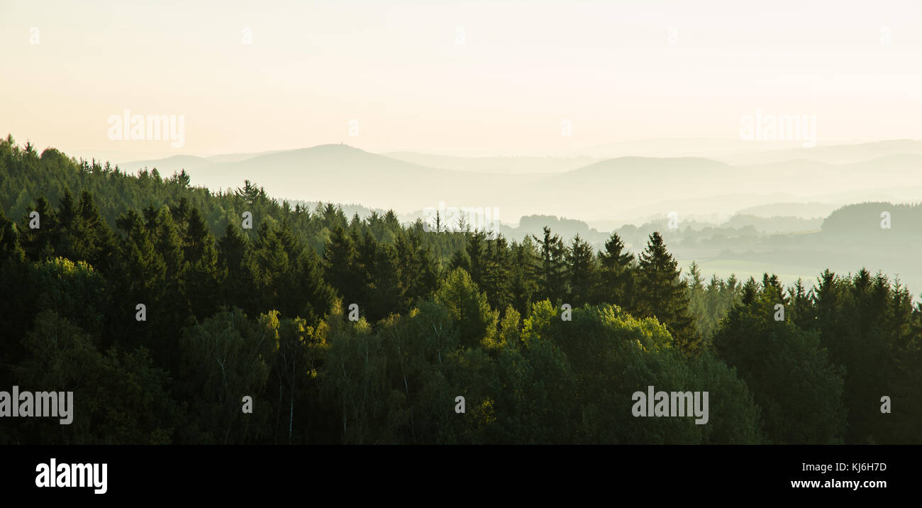 Sun and fog. Forceful contrast of sunlight and distant misty mountains. - Stock Image