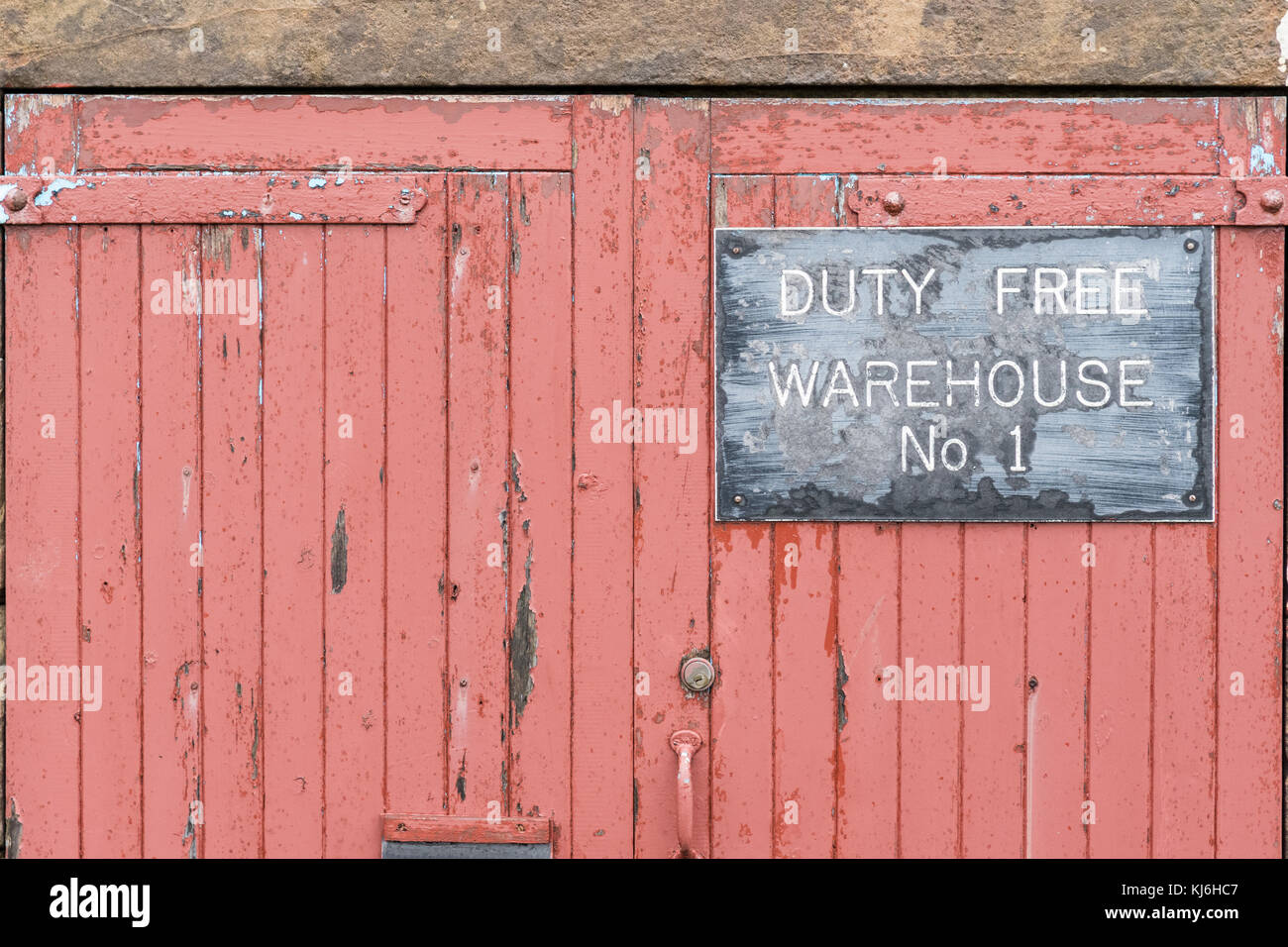 Duty Free Warehouse No 1 sign on faded red doors, Scapa whisky distillery, Orkney, Scotland, UK - Stock Image