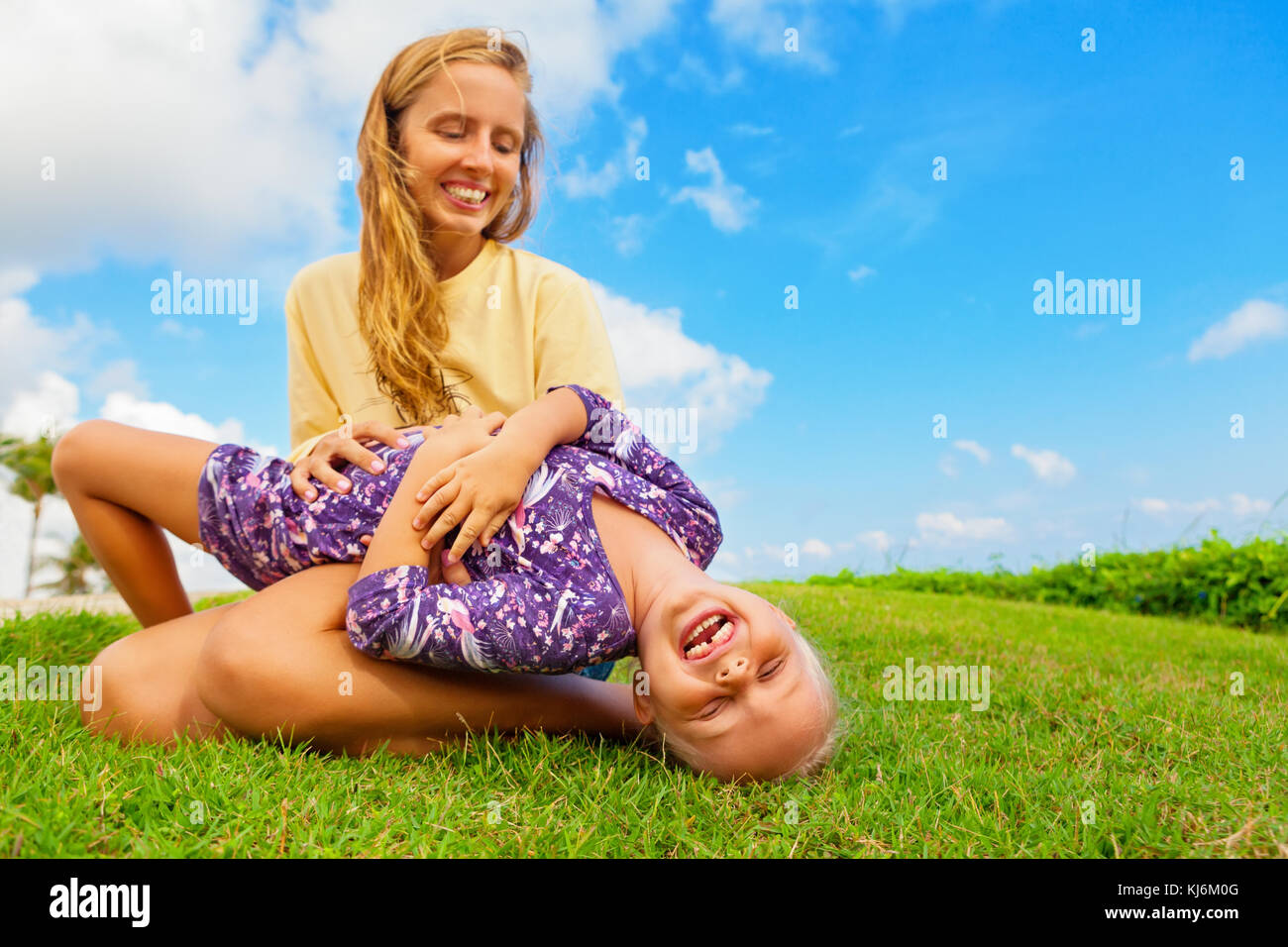Happy family on green grass lawn. Child have fun on outside walk - mother tickling funny baby son lying on her laps. - Stock Image