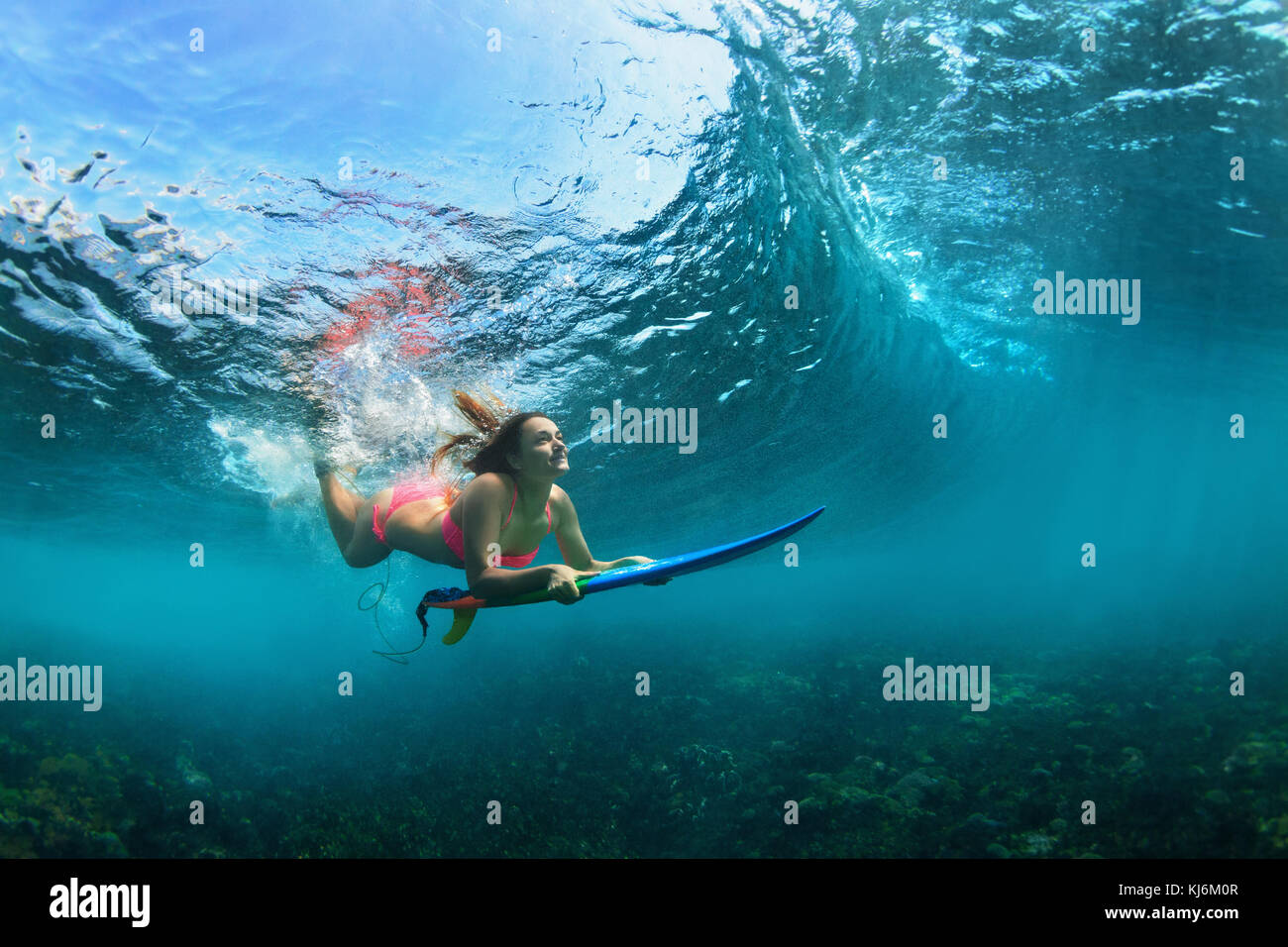 Active girl in bikini in action. Surfer woman with surf board dive underwater under breaking big wave. Teenage lifestyle. - Stock Image