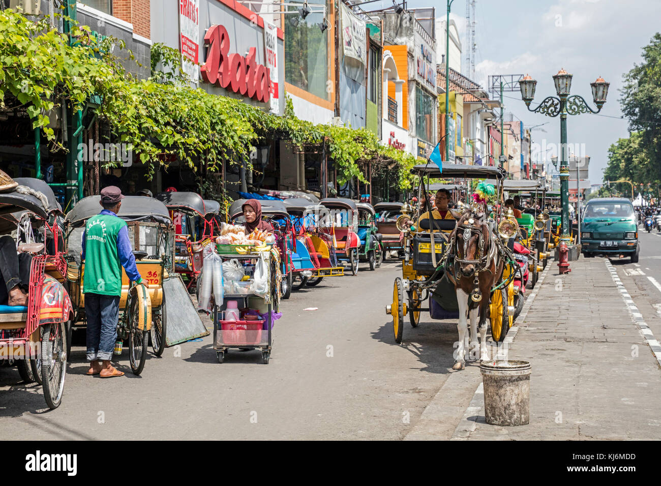 Cycle rickshaws / becak and horse-drawn carriages for public transport in Jalan Malioboro, major shopping street - Stock Image