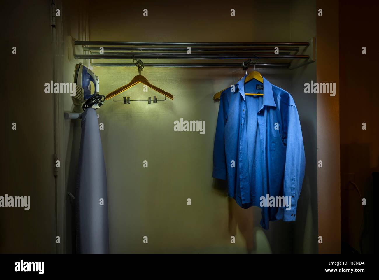 Blue Shirt Hanging In Motel Closet - Stock Image