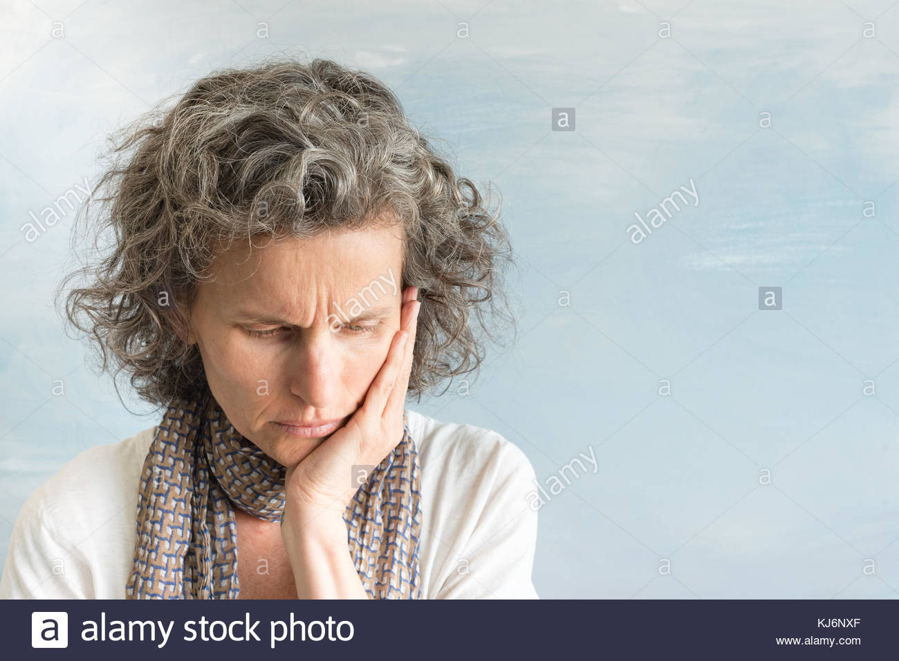 Middle aged woman with wavy grey hair and scarf frowning and looking down while holding face in concern (selective - Stock Image